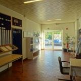 Eingangsbereich mit Sitzecke, Einheitentafel, Infomaterial und Playmobilvitrine